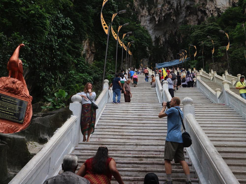 バトゥ洞窟の階段で立ち止まって記念撮影する人々